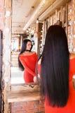 Schöne moderne junge Frau im Schönheitssalon, der im Spiegel nach Make-up und Haarpflege schaut lizenzfreie stockfotos