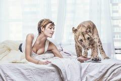 Schöne moderne junge Frau mit einem kleinen lebendigen Löwejungen Stockfotos