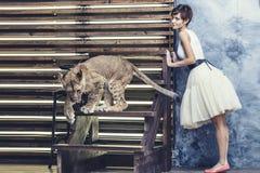 Schöne moderne junge Frau mit einem kleinen lebendigen Löwejungen Stockfoto