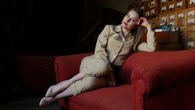 Schöne moderne sexy Luxusfrau in der beige Klage, die auf rotem Sofa liegt stock video footage