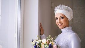 Schöne moslemische Braut mit bilden Blicke heraus das Fenster und das Lächeln lizenzfreies stockbild