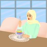 Schöne moslemische Frau, die Regenbogenkuchen im Restaurant isst Stockbild