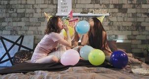 Schöne multi ethnische junge Damen brennen die Ballone beim die Geburtstagsfeier auf einem modernen Schlafzimmer zu Hause feiern  stock video footage