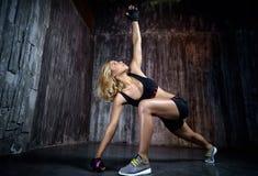 Schöne muskulöse Frau, die Übung auf einem grauen Hintergrund tut Stockfotografie