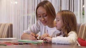 Schöne Mutter der jungen Frau zeichnet mit ihrer netten kleinen Tochter stock video