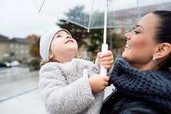 Schöne Mutter, die ihre kleine Tochter unter dem Regenschirm hält Lizenzfreie Stockfotos