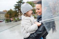 Schöne Mutter, die ihre kleine Tochter unter dem Regenschirm hält Lizenzfreies Stockbild
