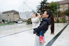 Schöne Mutter, die ihre kleine Tochter unter dem Regenschirm hält Lizenzfreie Stockfotografie