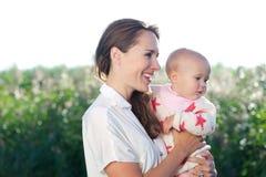 Schöne Mutter, die nettes Baby lächelt und hält Stockbilder
