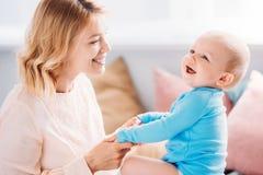 schöne Mutter, die Spaß mit lachendem Kind hat stockbild