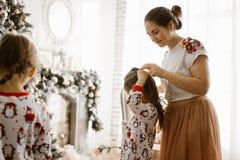 Schöne Mutter flicht die Borte ihrer kleinen Tochter im hellen gemütlichen Raum mit dem wunderbaren Baum des neuen Jahres lizenzfreies stockfoto