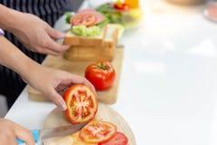 Schöne Mutter hackt Tomate, indem sie Messer auf Schneidebrett verwendet stockbild