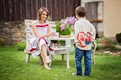Schöne Mutter, Kaffee in einem Hinterhof trinkend, junges nettes Kind-giv Lizenzfreie Stockfotografie
