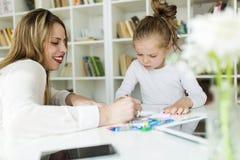 Schöne Mutter mit ihrer Tochterzeichnung mit Zeichenstiften zu Hause Stockfoto