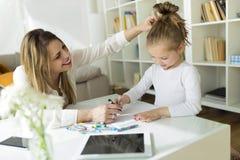 Schöne Mutter mit ihrer Tochterzeichnung mit Zeichenstiften zu Hause Lizenzfreie Stockfotos
