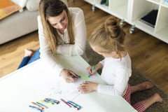 Schöne Mutter mit ihrer Tochterzeichnung mit Zeichenstiften zu Hause Stockfotos