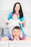 Schöne Mutter und glückliches Baby sitzen auf dem Vater, der auf Bett an ho liegt Lizenzfreie Stockfotos