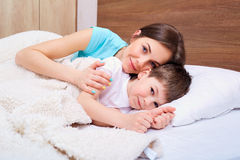 Schöne Mutter und ihr Sohn umfasst im Bett stockfotos
