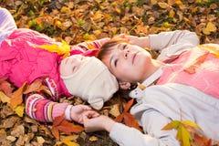 Schöne Mutter- und Kinderlage auf herbstlichen Blättern draußen Lizenzfreie Stockfotos