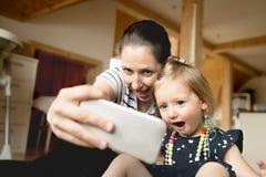 Schöne Mutter und kleine Tochter, die selfie mit smartpho nimmt Lizenzfreies Stockfoto