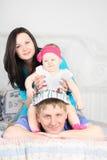 Schöne Mutter und nettes Baby sitzen auf Vater auf Bett Stockfotografie