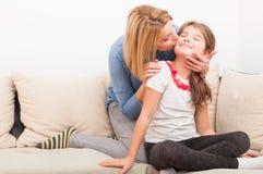 Schöne Mutter und Tochter auf der Couch oder dem Sofa Stockfoto