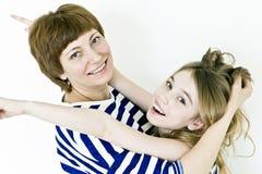 Schöne Mutter und Tochter auf Weiß Lizenzfreie Stockfotos
