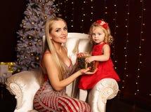 Schöne Mutter und Tochter, die zu Hause nahe Weihnachtsbaum aufwirft Lizenzfreies Stockfoto