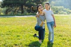 Schöne Mutter und Tochter, die zusammen ein selfie nimmt Lizenzfreies Stockbild