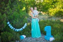 Schöne Mutterdamenmutter im stilvollen blauen Kleid zusammen mit ihrem Sohn- und Nummer Eins-Geburtstag im Park Lizenzfreies Stockbild