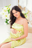 Schöne Mutterschaft Schwanger im zarten hellgrünen Kleid auf einem Sofa mit Lilien Lizenzfreie Stockfotos