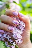 Schöne Nägel mit lila Blumen und frischen Blumen Lizenzfreie Stockfotografie