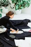 Schöne Näherin, schnitt schwarzes Gewebe auf dem Studioboden stockfotos