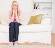 Schöne nachdenkliche Frau, die auf einem Sofa sitzt Lizenzfreies Stockbild