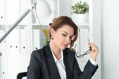Schöne nachdenkliche Geschäftsfrau, die an ihrem Arbeitsplatz sitzt Stockfoto