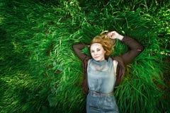 Schöne nachdenkliche junge Frau, die im Gras liegt. Sommer. Lizenzfreie Stockfotos