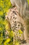 Schöne nackte Blondine unter gelben Blumen Stockfotografie