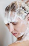 Schöne Nackte, die ihr Haar beim Nehmen der Dusche wäscht stockfotos