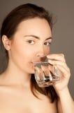 Schöne nackte Frau, die ein Wasser trinkt Stockbild