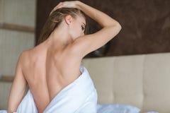 Schöne nackte Rückseite der verlockenden jungen Frau im Bett Stockbild