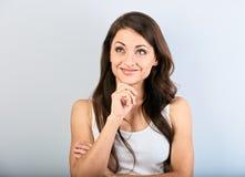 Schöne natürliche denkende lächelnde Frau mit der langen Frisur, die oben schaut Nahaufnahmeportr?t auf blauem Hintergrund stockfoto