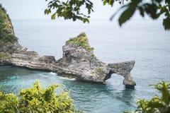 Schöne natürliche Felsen-Bogen-Insel im Meer an Atuh-Strand in Nusa Penida, Bali, Indonesien Schattenbild des kauernden Geschäfts stockfoto