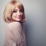 Schöne natürliche lächelnde blonde Frau, die in der Bluse ruhig schaut Zu Stockfotos