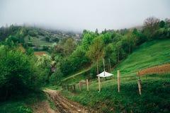 Schöne Naturgebirgslandschaft im Nebel Landstraße am sonnigen Morgen Standort - Karpatenberge, Ukraine lizenzfreies stockfoto