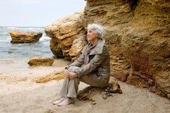 Schöne nette ältere Frau, die auf dem Strandmeer und -blicken in den Abstand nahe dem Meer sitzt Stockfotografie