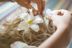 Schöne, nette blonde Braut, die Haar mit Blumen vor weddi tut Stockfotos