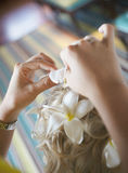 Schöne, nette blonde Braut, die Haar mit Blumen vor weddi tut Stockbilder