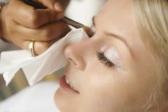 Schöne, nette blonde Braut, die Make-up vor Hochzeitstag tut lon Lizenzfreie Stockfotos