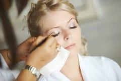 Schöne, nette blonde Braut, die Make-up vor Hochzeitstag tut lon Stockfotografie