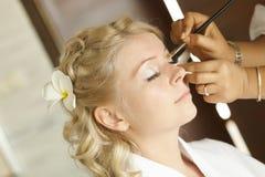 Schöne, nette blonde Braut, die Make-up vor Hochzeitstag tut lon Stockfoto
